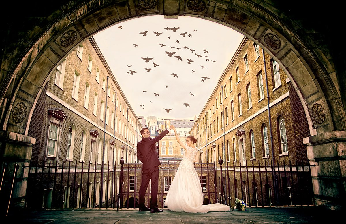 London wedding couple under arch with flying birds photo