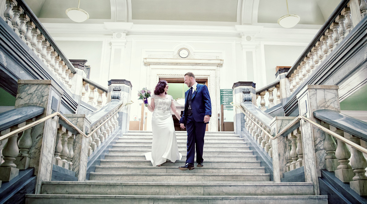 Wedding couple laugh on stairs at Islington Town Hall