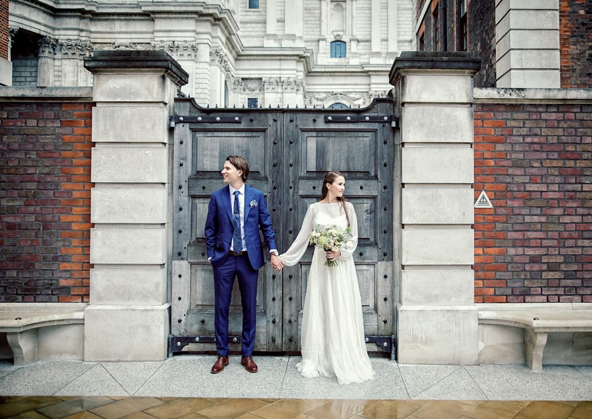 Central London wedding couple hold hands by St Pauls wooden gate