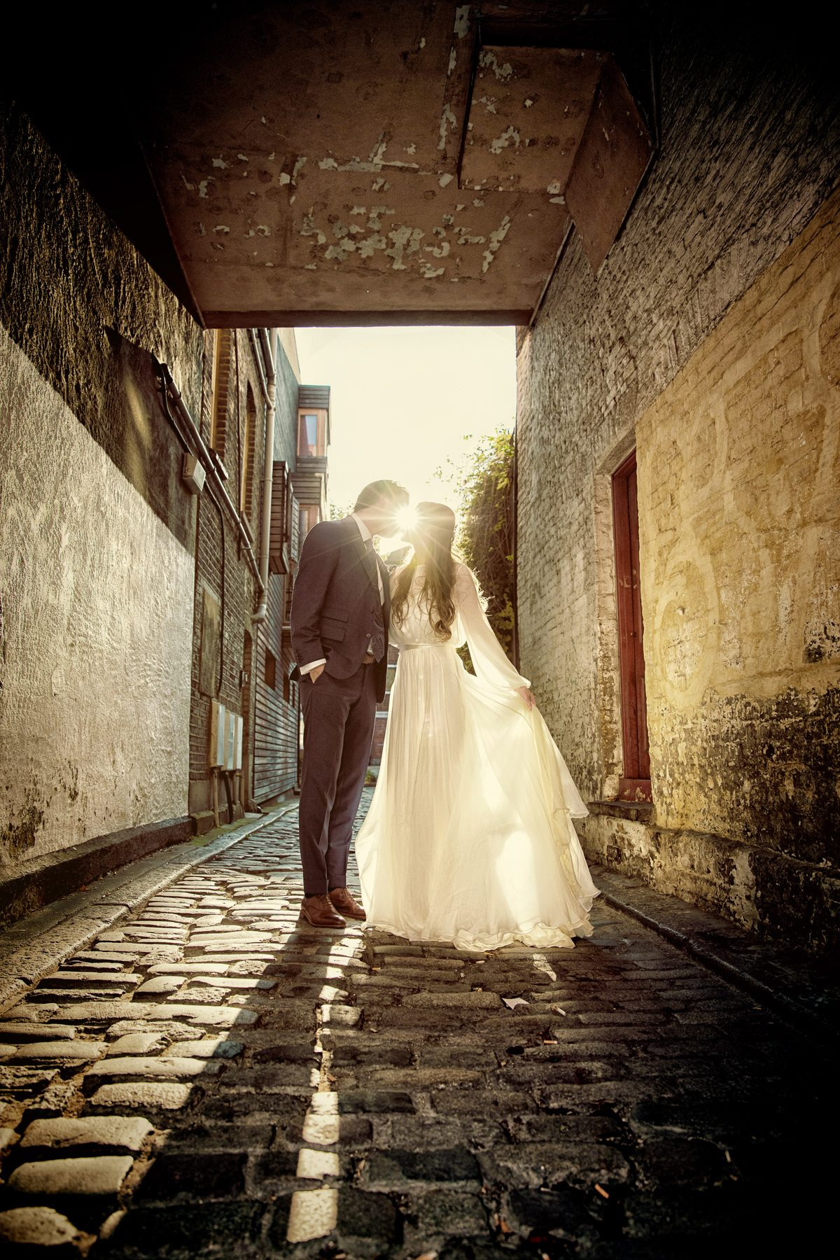 London wedding couple kiss in cobbled alley with sun flare