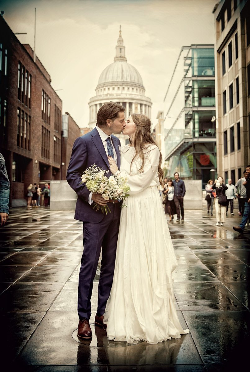 London wedding couple kiss in rain by St Pauls Cathedral
