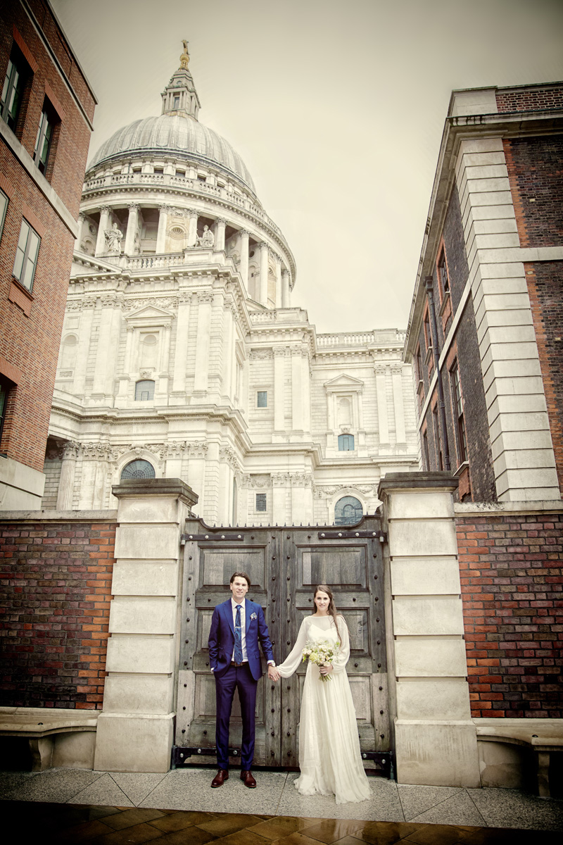 Wedding couple hold hands in Paternoster Square by St Pauls