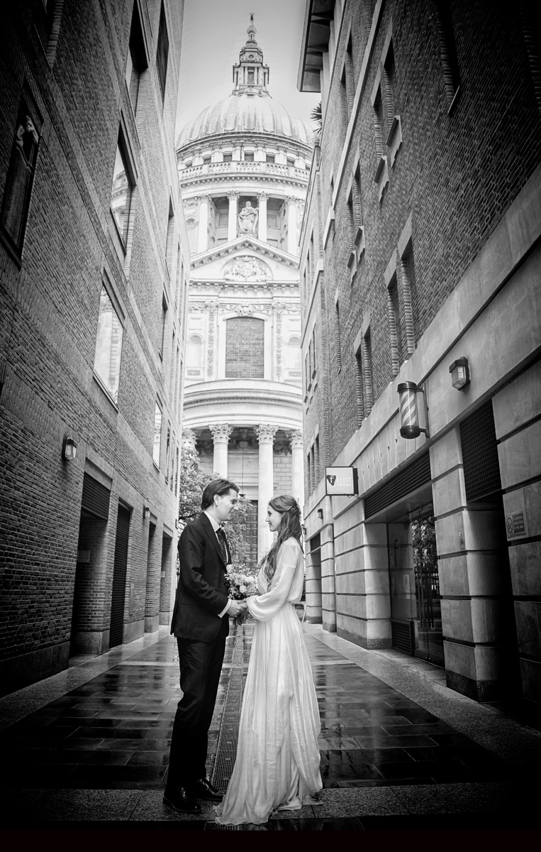 Wedidng couple hold hamds in front of St pauls Cathedral London