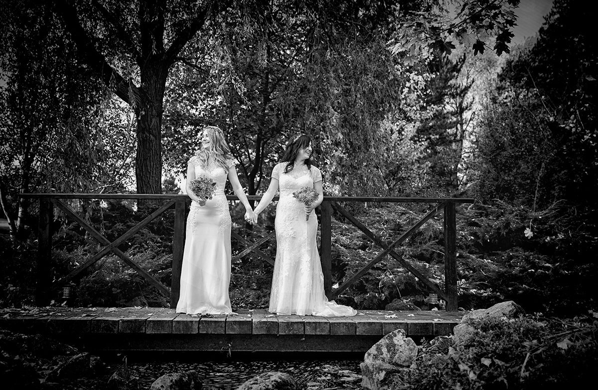 Two brides at their wedding hold hands on a bridge