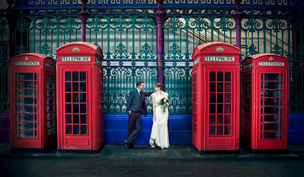 Couple by red phone boxes London wedding day Smithfield