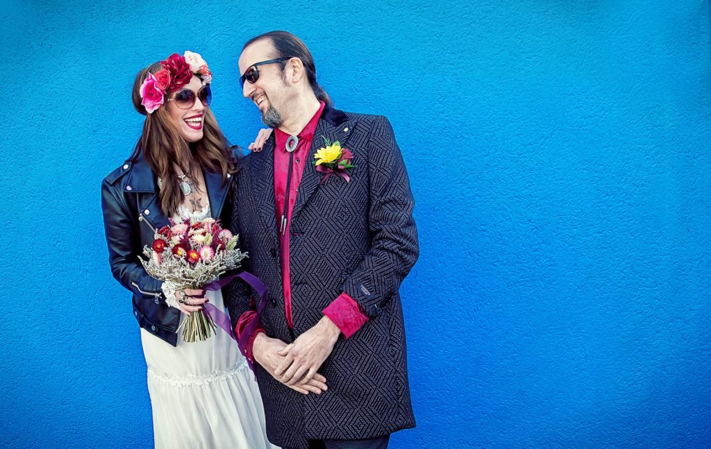 Islington wedding couple laugh by blue wall Upper Street London