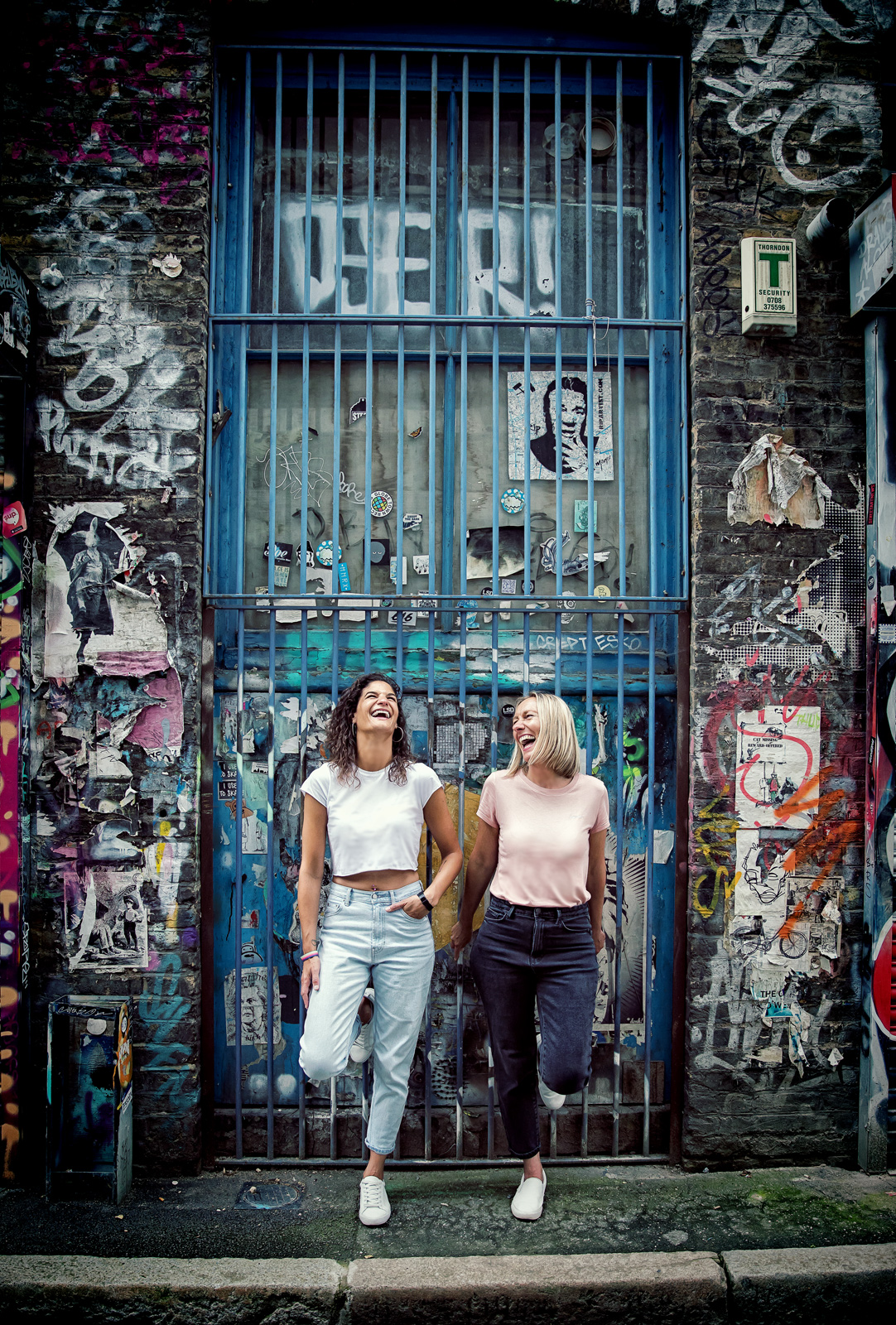 Shoreditch engagement shoot girls laugh by iron doors